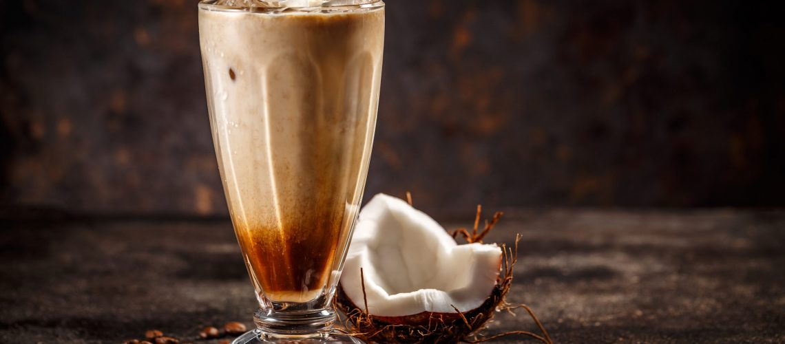 Glass of tasty coconut flavored coffee on vintage dark background